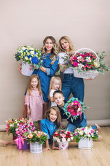 Group of people happy and beautiful, two mothers and their children holding flowers together on isolated background