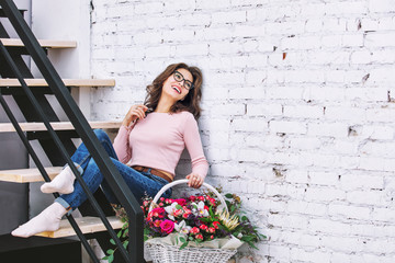 Young adult beautiful and happy woman model with flowers in her hands portrait on a bright staircase