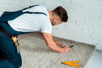 installer in overalls holding cutter near carpet