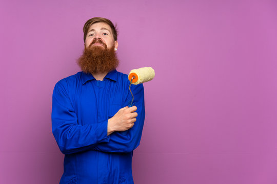 Painter man with long beard over isolated purple background