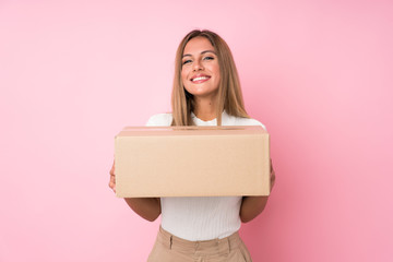 Young blonde woman over isolated pink background holding a box to move it to another site