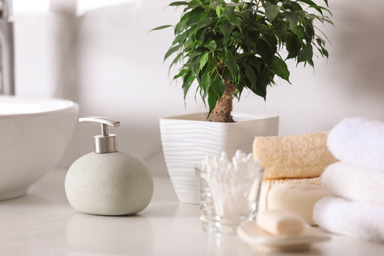 Composition with soap dispenser and towels on white table indoors