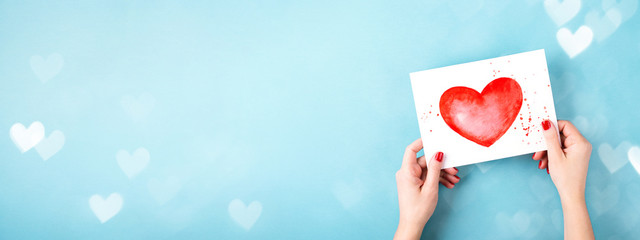 Female hands holding card with a painted red heart on blue background with bokeh. Minimal styled...