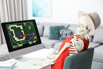 Human skeleton in red dress playing game at home