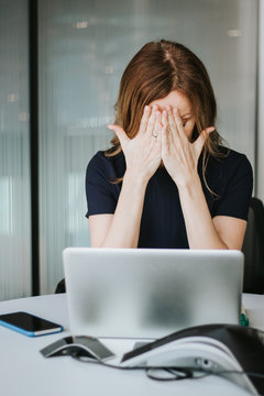 Portrait of modern beautiful tired business woman with headache covering face with hands working at laptop sitting at desk in office. Overworking hours, burnout concept.