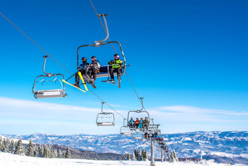 Skiers on chairlift at mountain ski resort with beautiful winter landscape in the background