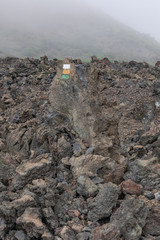 pathway colors sign on a volcanic rock, volcanic landscape with fog background, Santiago del Teide, Tenerife, Canary islands, Spain