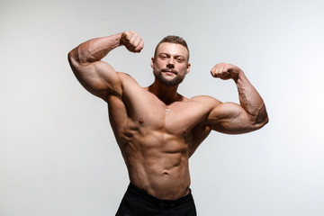 Young muscular bodybuilder guy demonstrates his muscles isolated on a light gray background.