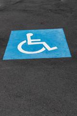 disabled parking blue/white sign, painted on asphalt surface