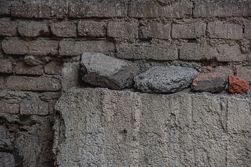 Old dark brick wall with stones
