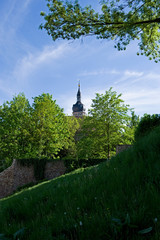 Altenburg / Germany: View over a green meadow and the remains of the old city wall to the octagonal baroque steeple of St. Bartholomew church