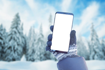 Phone mockup in hand with gloves. Winter, cold time with a lot of snow in mountain. Isolated screen...