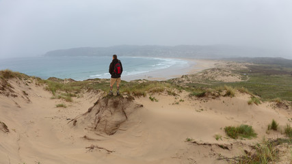 A hiker looks at a bay in the dunes of Prados in Galicia. Surfers are in the Atlantic and on the beach. It is hazy and it rains lightly. A winter day in the north of Spain.