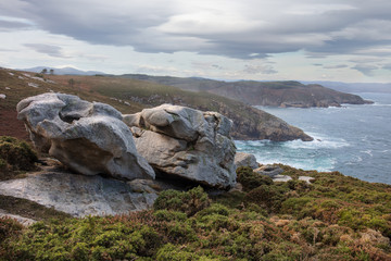 The wild Atlantic coast in northern Spain in Galicia at the Roncadoira lighthouse. In the foreground bizarre rocks and in the background the coastline by the ocean in haze.