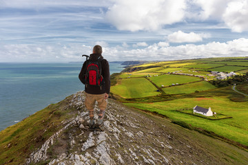 A hiker on the coastal path in Wales. The man looks at the sea. Below is the green land and a small white chapel. A cool and sunny day with a blue sky.