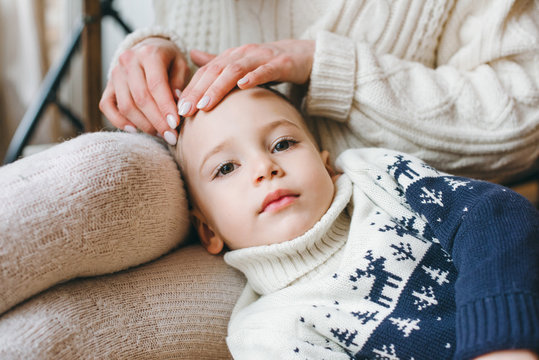 Mather and two little sons in knitted sweaters near a Christmas tree