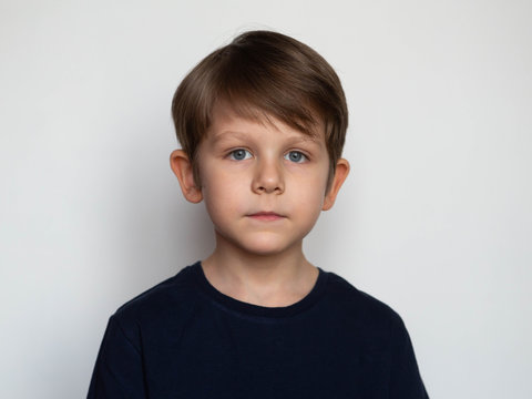 Portrait of a serious little boy on a white background