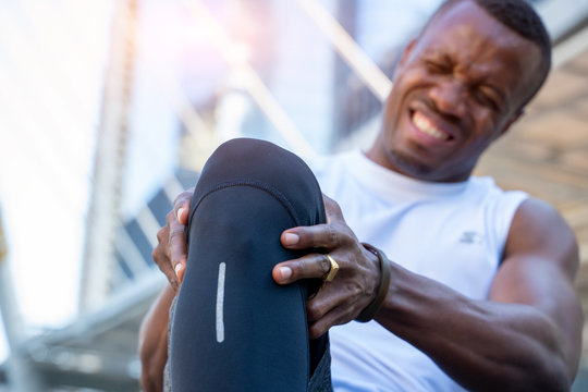African American male runner bends over clutching his knee while in intense pain from an acute knee injury,Athletes hurt the knees.