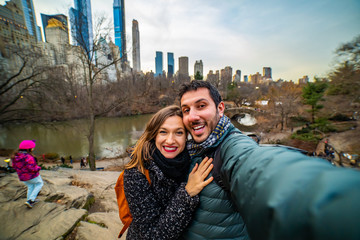 Beautiful happy couple taking selfie self-portrait on Brooklyn Bridge, New York. Hipster tourists having fun and photographing NY landmarks for travel blog. winter chrstmas time