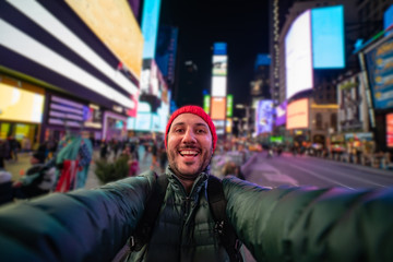 smiling young man taking a selfie with his smartphone on Times Square, New York. tourism in united states of America