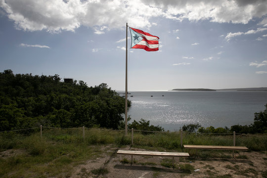 A Puerto Rican flag flies in front of the bay after the earthquake in Guayanilla