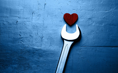 Wrench and red heart on a textured blue background.
