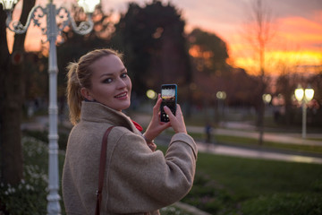 young russian woman takes photo with phone at sunset