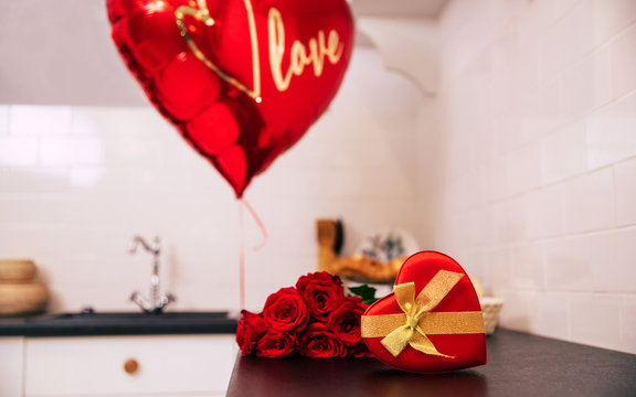 For my Valentine. Close-up photo of a bouquet of red roses, a big balloon and a red heart-shaped box with a golden ribbon, which lie on a kitchen table.