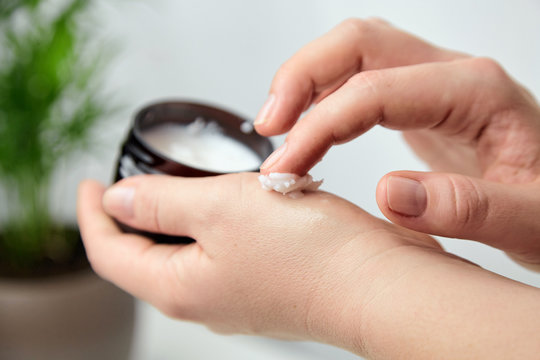 Shea butter in jar, cosmetic skin treatment product. Woman applying moisturizer to her skin of hand