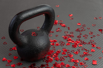 Holiday fitness, black kettlebell, with red heart confetti, on a black gym floor