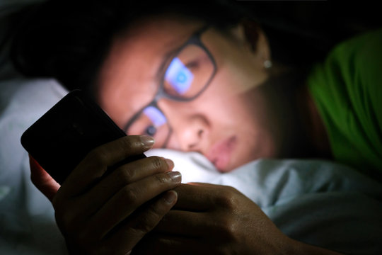 woman does not sleep and is stressed at night. She uses and looks smartphone in the bedroom without light and darkness.
