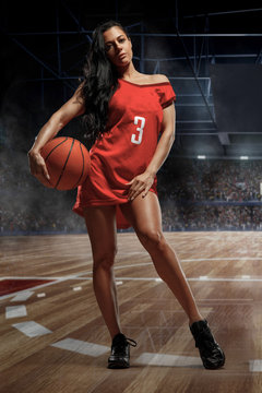 Young sexy girl player in basketball clothes with ball in gym. Sporty concept