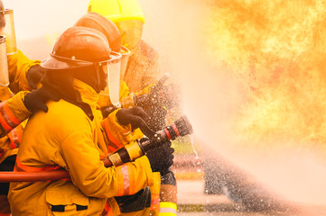 fireman fighting fire flame with water and extinguisher in training workshop, Teamwork and emergency concept