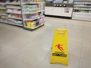 Obraz Yellow sign showing warning of caution wet floor. Wet floor sign is in the supermarket against the background of blurry products standing on the shelves. Selective focus. - fototapety do salonu