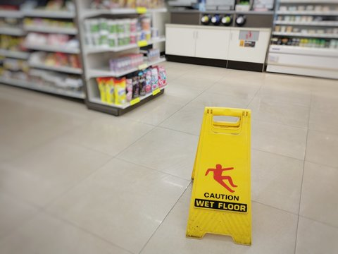 Yellow sign showing warning of caution wet floor. Wet floor sign is in the supermarket against the background of blurry products standing on the shelves. Selective focus.