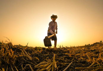 Elderly Asian farmers shoveling and prepare the soil with a spade for planting on sunset background.