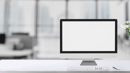 Cropped shot of simple workspace  with blank screen computer on white table with blurred office room