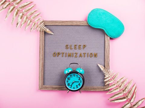 Sleep optimization text composed on wooden letter board with green sleeping mask, alarm clock, golden branches. Better healthy sleep tips concept