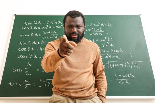 Angry African-American math teacher near blackboard in classroom
