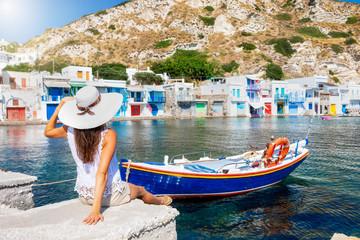 Eine Frau mit weißem Hut auf Reisen blickt auf das traditionelle Fischerdorf Klima mit den bunten Bootshäusern auf der Insel Milos, Kykladen, Griechenland Fotomurales
