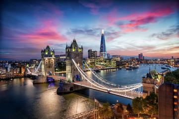 Blick auf die Tower Brücke und die Skyline von London mit den beleuchteten Hochhäusern an der...