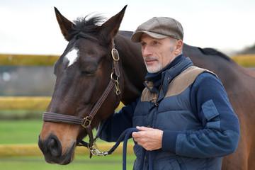 Portrait of horseman standing by horse Papier Peint