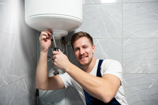 young handsome smiling man worker in uniform with screwdriver in his hand repairing water heater at home in the toilette professional repair service