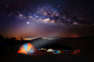 Camping and tent under the with forest near in the mountains . A tent pitched up and glowing under the milky way