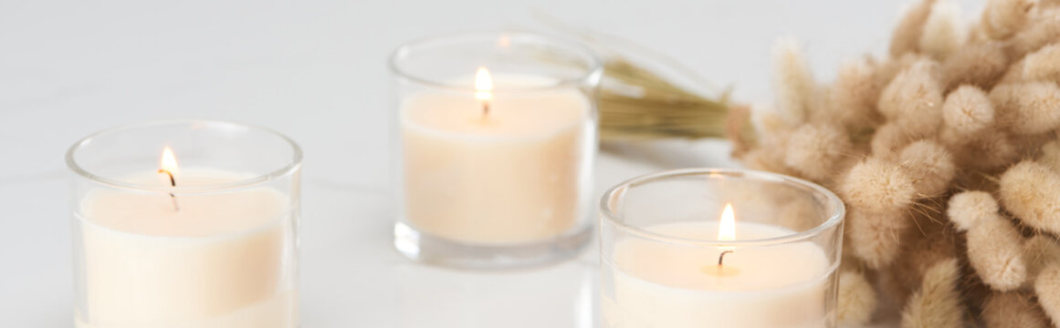 selective focus of fluffy bunny tail grass and burning white candles in glass glowing on marble white surface, panoramic shot