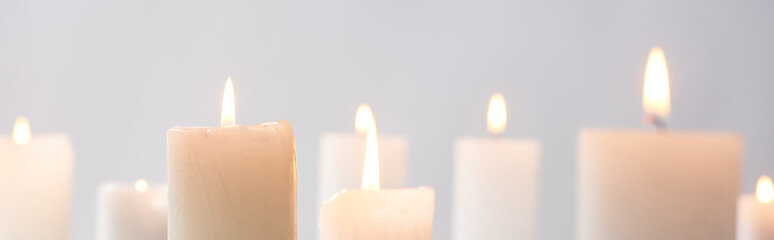 Foto op Aluminium Europa selective focus of burning white candles glowing isolated on grey, panoramic shot