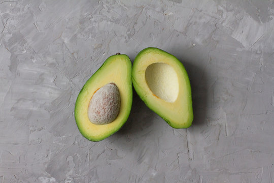 sliced avocado. avocado fruit on a gray background with a stone. healthy fruits and vegetables. the view from the top. ingredients for making salad. space for text. the concept of diet