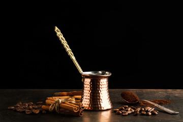 Cafetera Turca y Café en granos y molido sobre fondo oscuro. Vista de frente