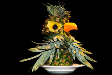 Pineapple, decorated in the technique of carving.  Carving in cooking is the art of artistic cutting of vegetables and fruits. Examples of ornaments for dishes made in the carving technique.