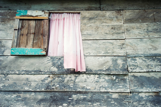 Weathered wood shack background with pink curtain billowing out an open window